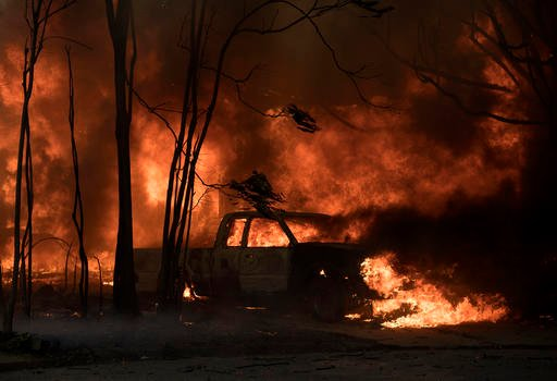 A truck burns in the town of Lower Lake, Calif. on Sunday, Aug. 14, 2016. Flames continue to burn out of control in the area. (AP Photo/Josh Edelson)