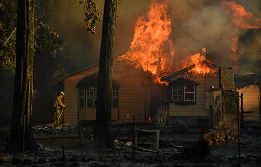 In this Sunday, Aug. 14, 2016, photo, a firefighter battles flames as a house is engulfed in the town of Lower Lake, Calif. (AP Photo/Josh Edelson)