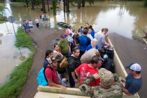 Sgt. Brad Stone of the Louisiana Army National Guard gives safety instructions to people loaded on a truck after they were stranded by rising floodwater near Walker, La. (AP Photo/Max Becherer)