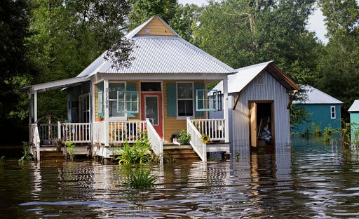Floodwaters reach the front steps of a home near Holden, La., after heavy rains inundated the region, Sunday, Aug. 14, 2016. (AP Photo/Max Becherer)
