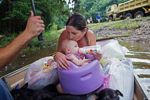 Danielle Blount kisses her 3-month-old baby Ember as she feeds her while they wait to be evacuated by members of the Louisiana Army National Guard near Walker, La.(AP Photo/Max Becherer)