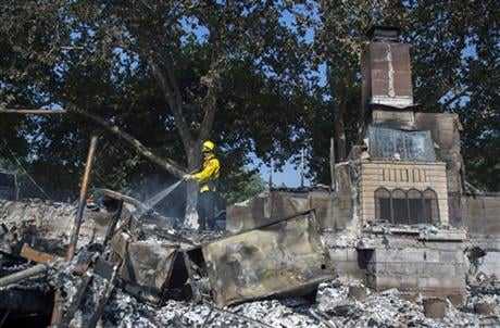 Dan Peters, with the Nevato Fire District, mops up a fire at a house during the Clayton fire after structures were destroyed in Lower Lake, Calif., Monday, Aug. 15, 2016. (Hector Amezcua/The Sacramento Bee via AP)