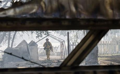 A firefighter walks through a burned property as multi-agency fire crews mop up the Clayton fire after structures were destroyed in Lower Lake, Calif., Monday, Aug. 15, 2016. (Hector Amezcua/The Sacramento Bee via AP)