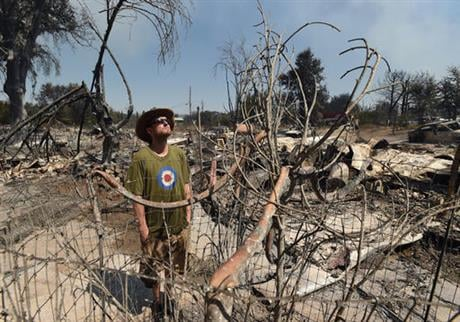 James McCauley looks over the burned-out remains of his residence in the town of Lower Lake, Calif., Monday, Aug. 15, 2016. (AP Photo/Josh Edelson)