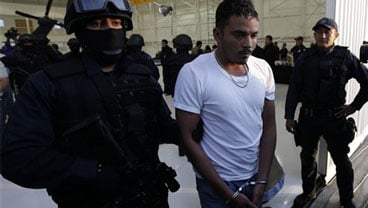 Federal police escort handcuffed suspect Jose Roberto de la Sancha as he his presented to the press in Mexico City, Thursday, Oct. 22, 2009. (AP Photo/Gregory Bull)
