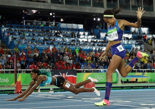 Bahamas' Shaunae Miller falls over the finish line to win gold ahead of United States' Allyson Felix, right, in the women's 400-meter final.