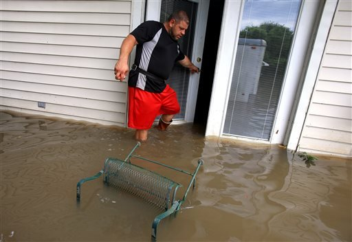 Wade Gary exits his home after viewing the damage in his studio apartment from floodwater.