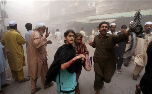 People rush after an explosion in Peshawar, Pakistan on Wednesday Oct. 28, 2009. A car bomb tore through a market in northwestern Pakistan on Wednesday, hours after U.S. Secretary of State Hillary Rodham Clinton arrived in the country.(AP Photo/Mohammad)
