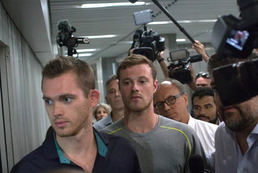Journalists surround American Olympic swimmers Gunnar Bentz, left, and Jack Conger, center, as they leave the police station at Rio International airport.
