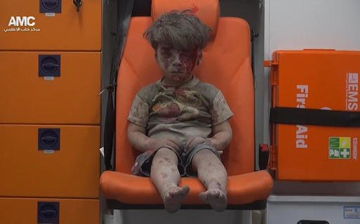 A child sits in an ambulance after being pulled out or a building hit by an airstirke, in Aleppo, Syria.