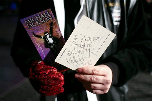 """A fan of Michael Jackson shows the King of Pops' autograph and a card for his concert in London in 2009 prior the premiere of the documentary """"This Is It"""" in Berlin, Germany, late Tuesday, Oct. 27, 2009."""