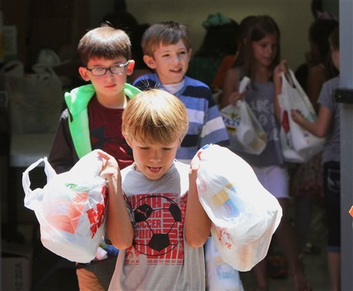 In this Tuesday, Aug., 16, 2016, photo, Bayou View Elementary School second grader Ethan Borderon, 8, and other classmates load cleaning supplies at the Gulfport, Miss., school for flood victims in Louisiana. The city of Gulfport collected three truck loa