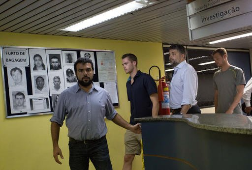 Accompanied by Brazilian lawyer Sergio Riera, second from right, American Olympic swimmers Gunnar Bentz, center, and Jack Conger, right, leave the police station at Rio International airport early Thursday Aug. 18, 2016.