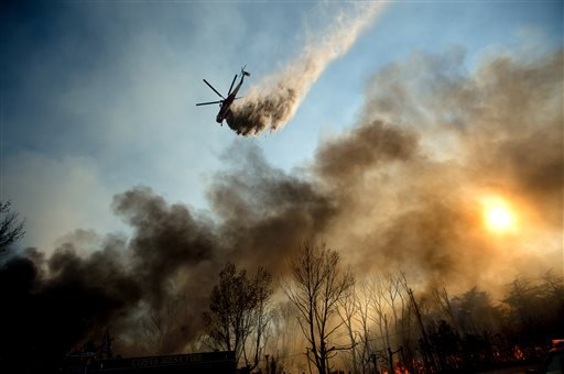 A helicopter drops water on a wildfire as it burns through Keenbrook, Calif.