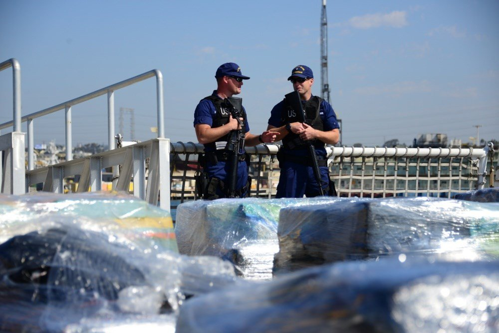 The crew of the Coast Guard Cutter Sherman guards pallets of cocaine prior to offloading them at Naval Base San Diego on August 18, 2016. Approximately 11 tons were offloaded after being seized in the Eastern Pacific. (U.S. Coast Guard photo by Fireman Ta