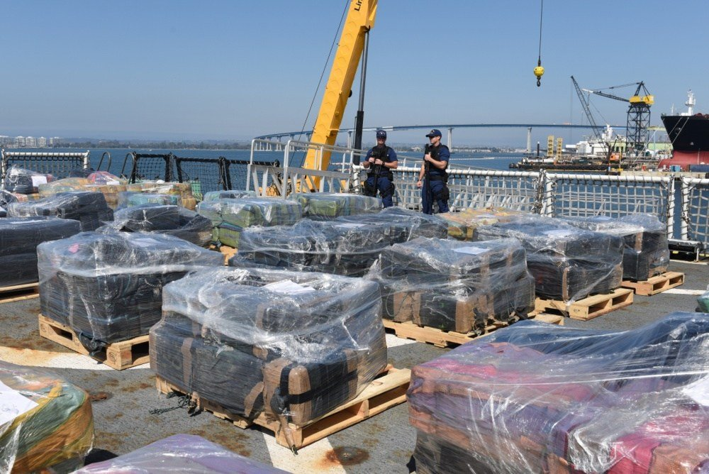 The crew of the Coast Guard Cutter Sherman guards pallets of cocaine prior to offloading them at Naval Base San Diego on August 18, 2016. Approximately 11 tons were offloaded after being seized in the Eastern Pacific. (U.S. Coast Guard photo by Petty Offi