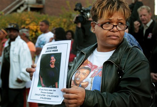 Patricia Warren of Cleveland holds up a missing persons poster of her cousin Janice Webb, missing since June of this year, outside the home of Anthony Sowell on Friday, Oct. 30, 2009 in Cleveland. (AP Photo/The Plain Dealer, John Kuntz)