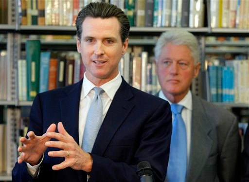 San Francisco Mayor Gavin Newsom, left, is joined by former U.S. President Bill Clinton, right, at Los Angeles City College's new Science and Technology Building. (AP Photo/Damian Dovarganes)