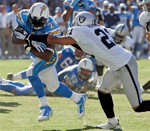 San Diego Chargers running back LaDainian Tomlinson, left, breaks free from Oakland Raiders' Nnamdi Asomugha, right, on a 10-yard touchdown run during the second quarter of a NFL football game Sunday, Nov. 1, 2009 in San Diego.