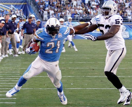 San Diego Chargers running back LaDainian Tomlinson breaks away from Oakland Raiders' Thomas Howard, right, on an eight-yard run during the fourth quarter of an NFL football game on Sunday, Nov. 1, 2009 in San Diego.