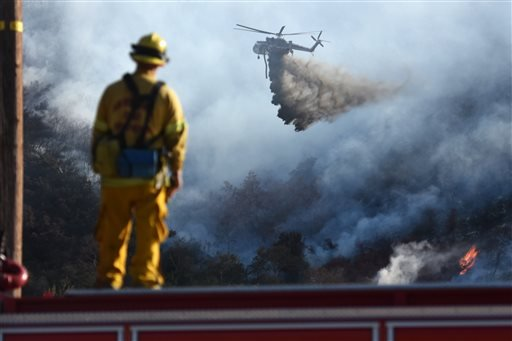 A San Bernardino County Fire Department firefighter watches a helitanker make a water drop on a wildfire, seen from Cajon Boulevard in Devore, Calif., Thursday, Aug. 18, 2016. (David Pardo/The Daily Press via AP)
