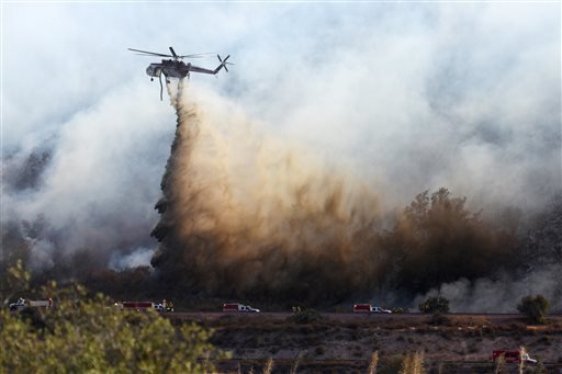 A helitanker does a water drop on hot spots during a wildfire near Cajon Boulevard in Devore, Calif., Thursday, Aug. 18, 2016. (David Pardo/The Daily Press via AP)