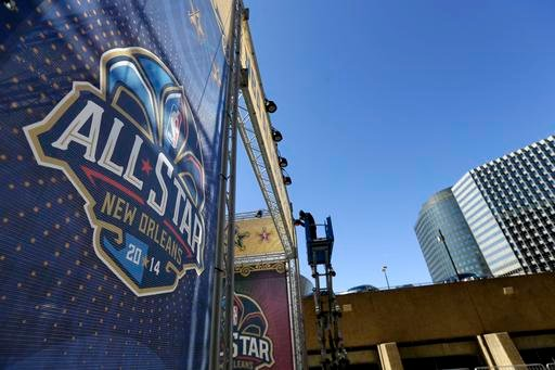 In this Feb. 13, 2014, file photo, a worker attaches a banner to a scaffolding in New Orleans in preparation of the NBA All-Star basketball game.