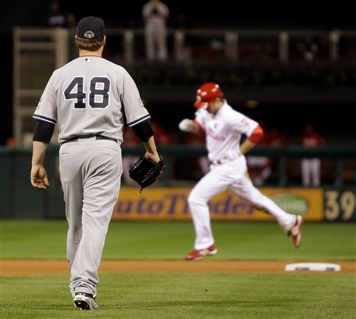 New York Yankees' Phil Coke watches as Philadelphia Phillies' Chase Utley rounds the bases after Utley hit a home run during the seventh inning of Game 5 of the Major League Baseball World Series. (AP Photo/Matt Slocum)