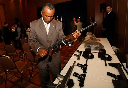 John Torres, Special Agent in Charge of the Bureau of Alcohol, Tobacco, Firearms, and Explosives inspects a 50 caliber rifle. (AP Photo/Lenny Ignelzi)