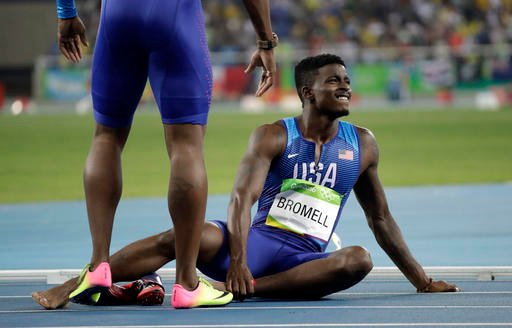 United States' Trayvon Bromell sits on the track after falling in the men's 4x100-meter relay final.