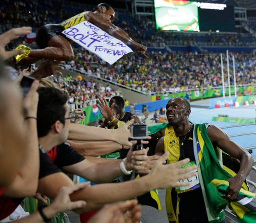 Jamaica's Usain Bolt greets fans as he celebrates winning gold in the men's 4 x 100-meter relay final.