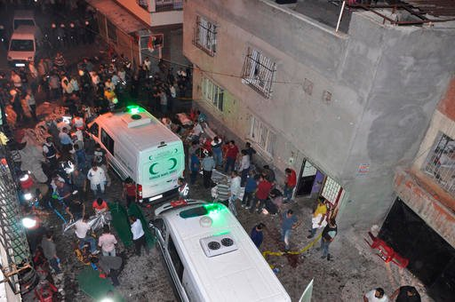People carry dead bodies into ambulances after an explosion in Gaziantep, southeastern Turkey, early Sunday, Aug. 21, 2016. A bomb attack targeting an outdoor wedding party in southeastern Turkey killed several people and wounded dozens. Deputy Prime Mini
