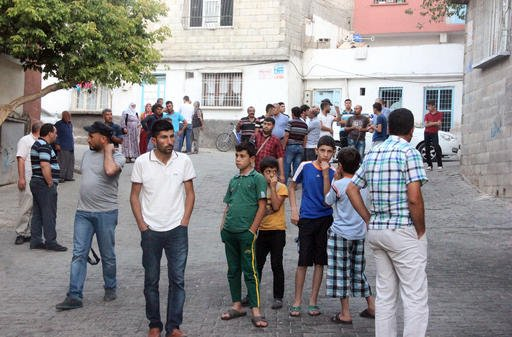 People gather to view damage just hours after Saturday's bomb attack in Gaziantep, southeastern Turkey, early Sunday, Aug. 21, 2016, targeting an outdoor wedding party in southeastern Turkey killed dozens of people and wounded dozens. Deputy Prime Ministe