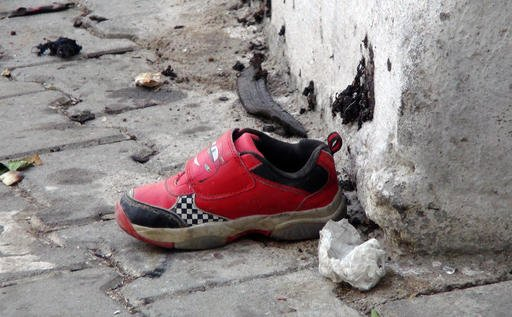 The shoe of a young victim and a piece of metal lay near the scene just hours after Saturday's bomb attack in Gaziantep, southeastern Turkey, early Sunday, Aug. 21, 2016, targeting an outdoor wedding party in southeastern Turkey killing dozens of people a