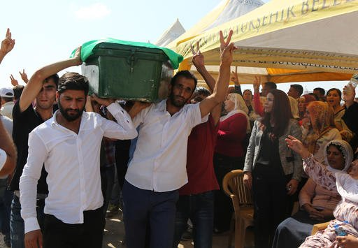 """People mourn as they attend funeral services for dozens of people killed in last night's bomb attack targeting an outdoor wedding party in Gaziantep, southeastern Turkey, Sunday, Aug. 21, 2016. Deputy Prime Minister Mehmet Simsek said the """"barbaric"""" attac"""
