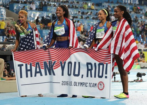United States' Courtney Okolo, Natasha Hastings, Phyllis Francis and Allyson Felix hold a sign and wear their nation's flag after winning the gold in the women's 4x400 meter relay during athletics competitions at the Summer Olympics inside Olympic stadium