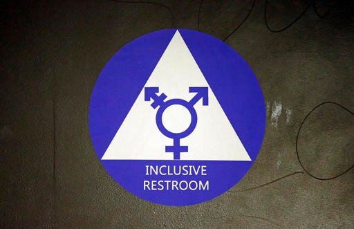 In this May 17, 2016, file photo, a new sticker designates a gender neutral bathroom at Nathan Hale high school in Seattle. A federal judge in Texas is blocking for now the Obama administration's directive to U.S. public schools that transgender students