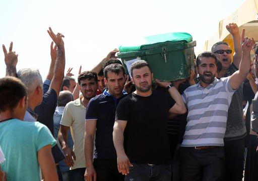 People carry a victim's coffin as they attend funeral services for dozens of people killed in last night's bomb attack targeting an outdoor wedding party in Gaziantep, southeastern Turkey, Sunday, Aug. 21, 2016. Deputy Prime Minister Mehmet Simsek said th
