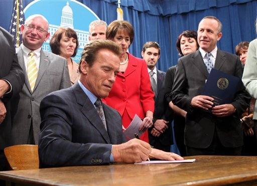 Gov. Arnold Schwarzenegger signs a measure to restore $16.3 million in one-time funding for domestic violence shelters at the Capitol in Sacramento on Oct. 21. ((AP Photo/Rich Pedroncelli)