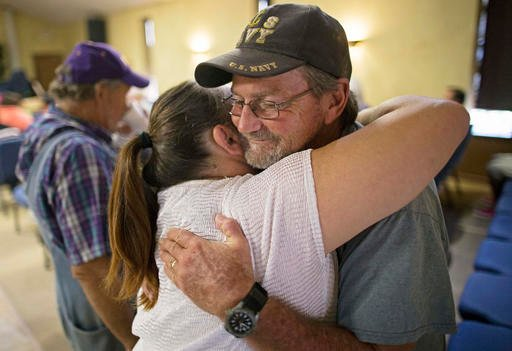 Charles Craft, 57, right, gets a hug from Tammie Lovelady, 49, before church service at South Walker Baptist Church in Walker, La.