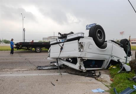 In this April 28, 2016 file photo, a wrecker crew prepares to flip over a Ford Bronco that was involved in an accident in Brownsville, Texas. (Jason Hoekema/The Brownsville Herald via AP, File)