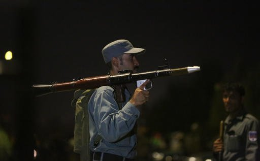 An Afghan policeman holds a rocket-propelled grenade launcher at the site of a complex Taliban attack on the campus of the American University in the Afghan capital Kabul on Wednesday, Aug. 24, 2016. University President Mark English told The Associated P