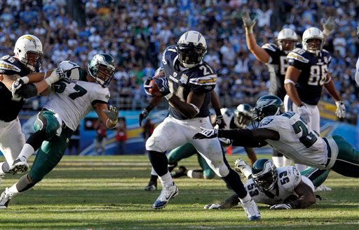 San Diego Chargers running back LaDainian Tomlinson slips through the Philadelphia Eagles defense while scoring on a 20-yard run during the third quarter of a NFL football game Sunday, Nov. 15, 2009 in San Diego. (AP Photo/Denis Poroy)