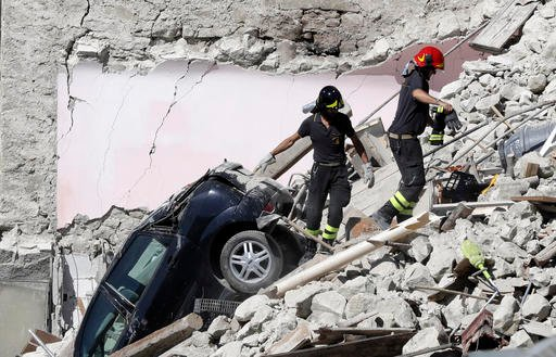 Rescuers make their way through destroyed houses following Wednesday's earthquake in Pescara Del Tronto, Italy, Thursday, Aug. 25, 2016.