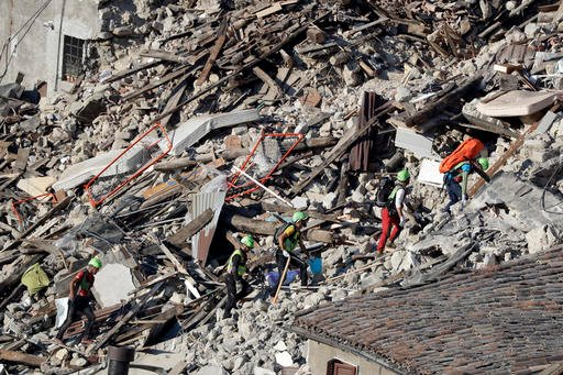 Rescuers make their way through destroyed houses following an earthquake in Pescara Del Tronto, central Italy, Thursday, Aug. 25, 2016.