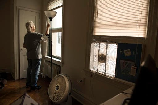 """In this Tuesday, Aug. 16, 2016, photo, Wanda Witter draws the blinds in her new apartment in Washington. Social workers from Street Sense helped her shop for her """"micro apartment,"""" an efficiency with no air conditioning. Witter has been trying to prove th"""