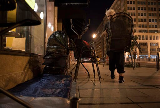 In this Aug. 10, 2016, photo, Wanda Witter, who is homeless, moves dining tables and chairs into a protective blockade at her sleeping spot outside the Au Bon Pain on 13th and G Street in Washington. Witter, 80, was recently attacked at the location, suff