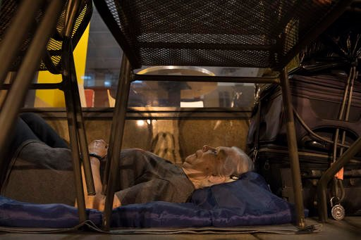 In this Aug. 10, 2016, photo, with suitcases in arms reach, Wanda Witter, who is homeless, beds down in her sleeping spot outside the Au Bon Pain on 13th and G Street in Washington. Witter, 80, was recently attacked at the location, suffering a black eye