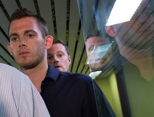 In this early Thursday, Aug. 18, 2016 American Olympic swimmers Gunnar Bentz, left, and Jack Conger, leave the police station at the international airport in Rio de Janeiro, Brazil. The two were taken off their flight from Brazil to the U.S. on Wednesday