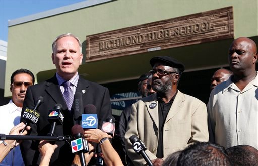 In this Nov. 2, 2009 file photo, Richmond Police chief Chris Magnus, second from left, speaks at Richmond High School in Richmond, Calif., during a rally against the gang rape of a 15-year-old girl. (AP Photo/Jeff Chiu, file)